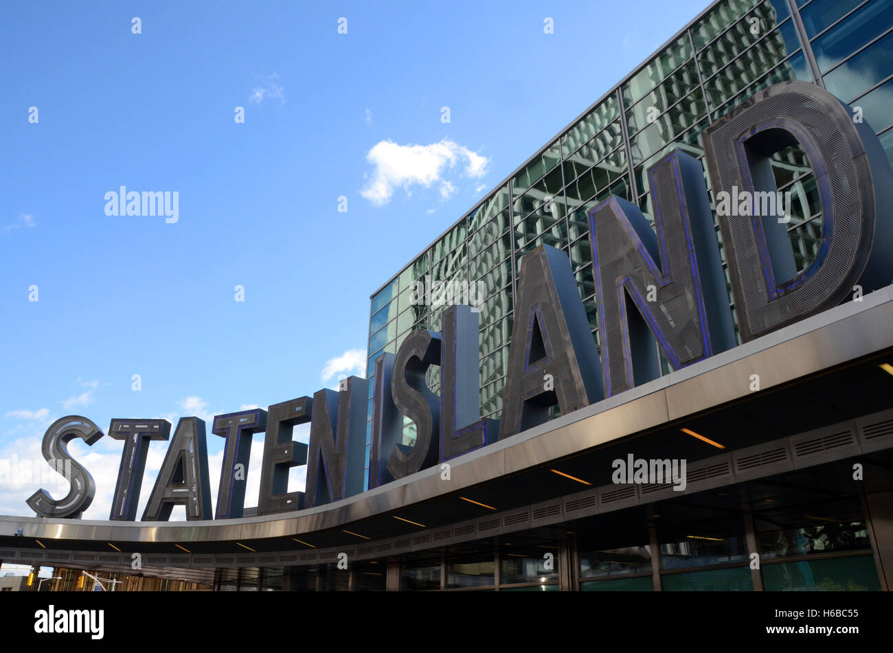staten island ferry terminal building sign on sunny day blue sky metal with neon lights simon leigh - Stock Image