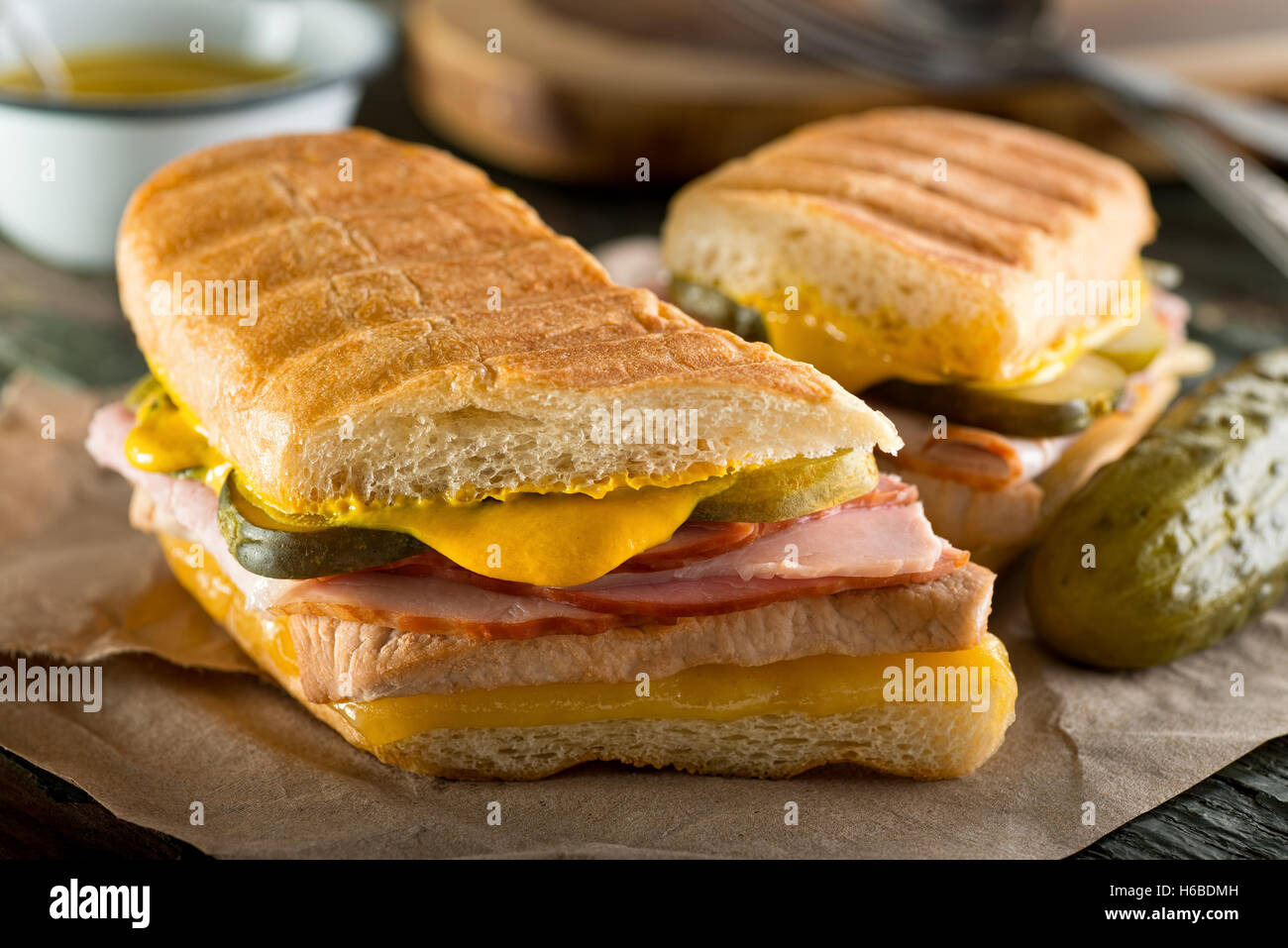 An authentic cuban sandwich on pressed medianoche bread with pork, ham, cheese, pickle, and mustard. - Stock Image