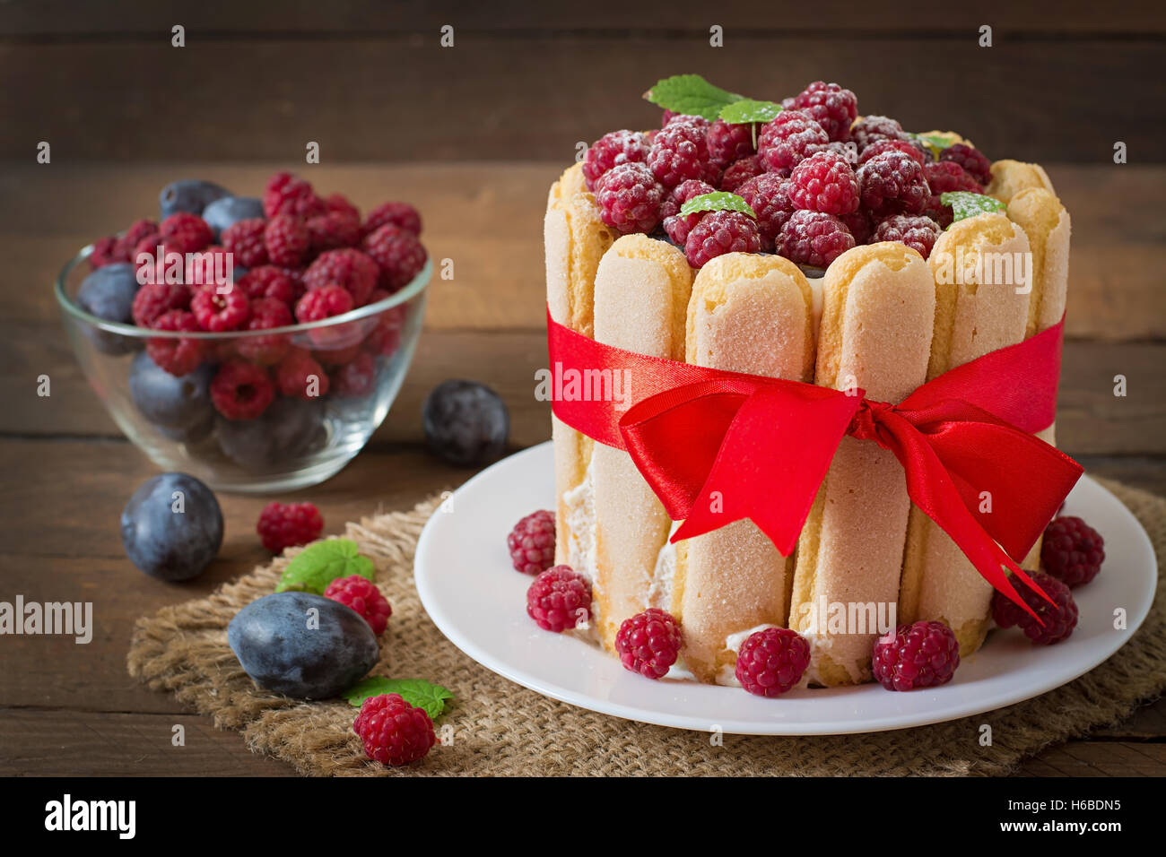 Cake 'Charlotte ' with raspberries and plums. - Stock Image