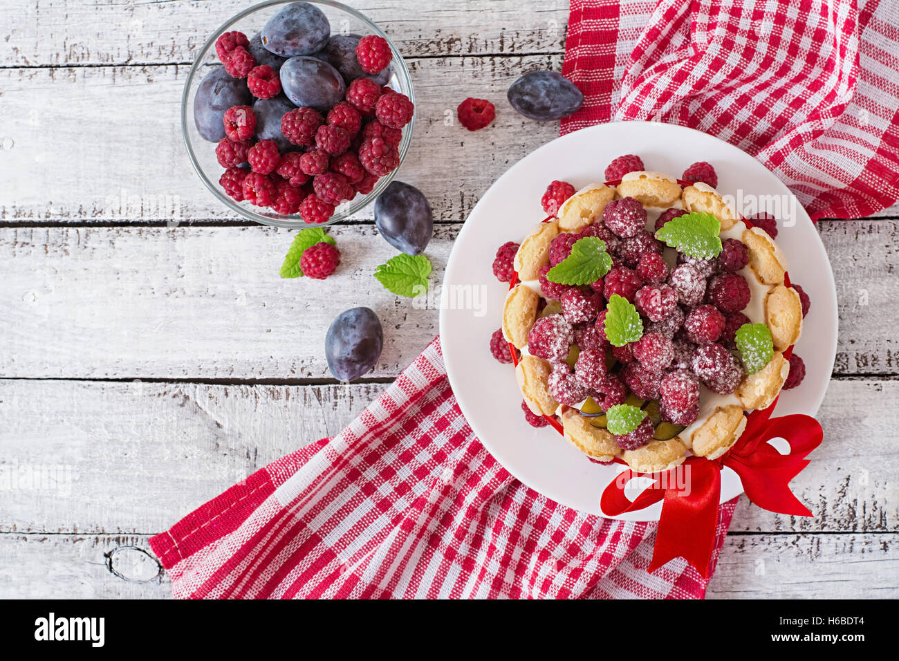 Cake 'Charlotte ' with raspberries and plums. Top view - Stock Image