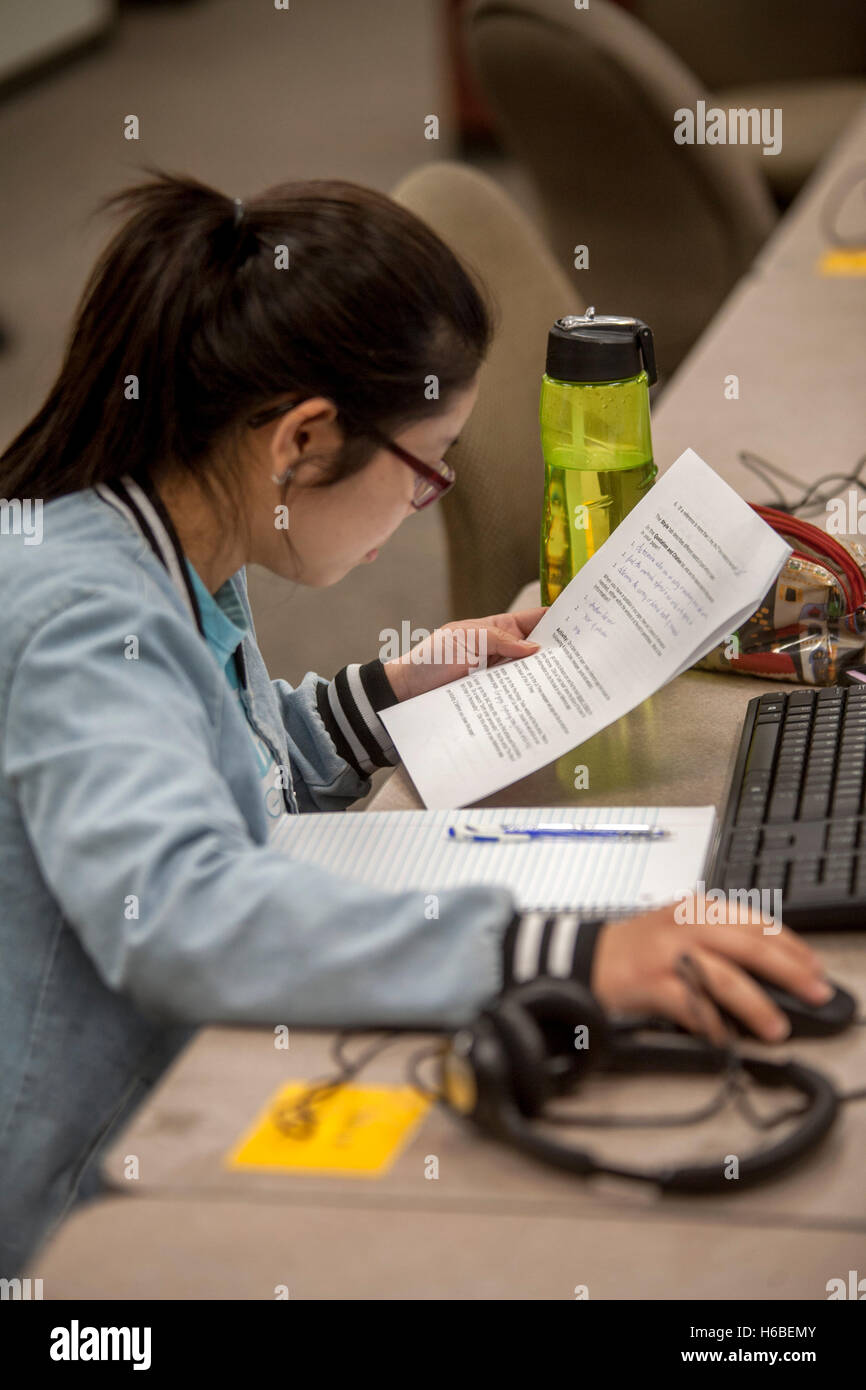 A Hispanic young adult community college student peruses a Directed Learning Assignment in Santa Ana, CA. A DLA - Stock Image