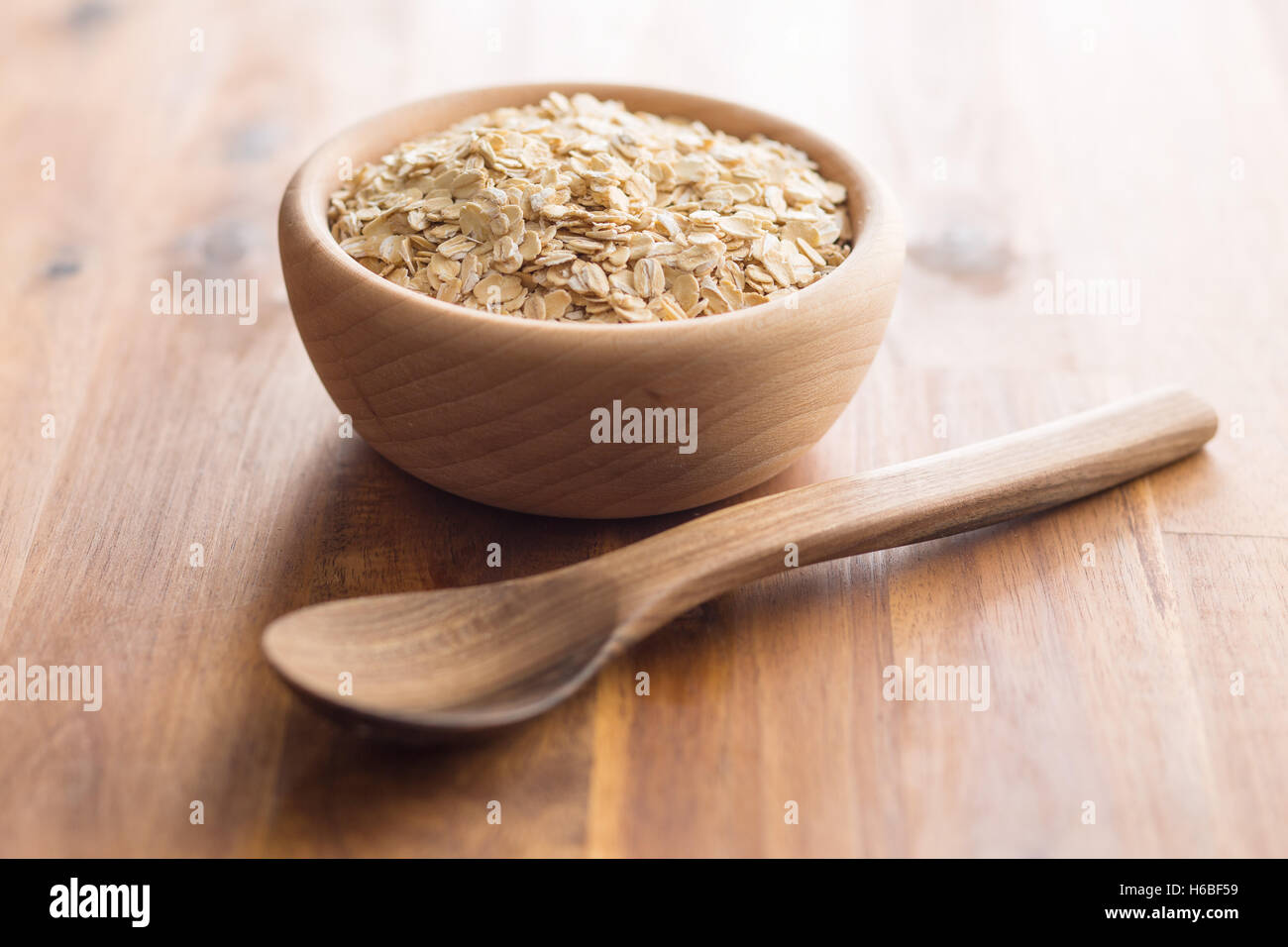 Dry rolled oatmeal in wooden bowl. - Stock Image