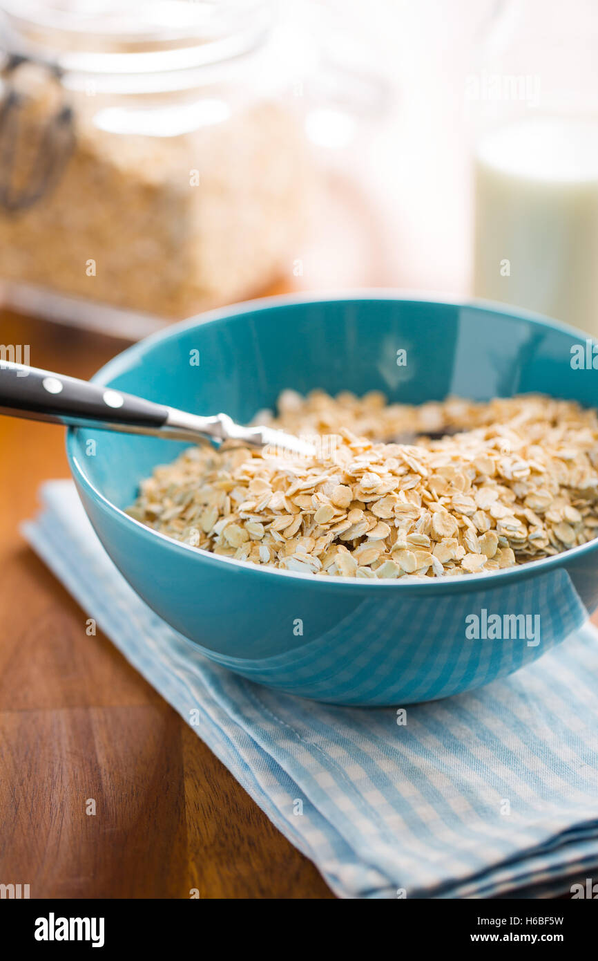 Dry rolled oatmeal in blue bowl. - Stock Image