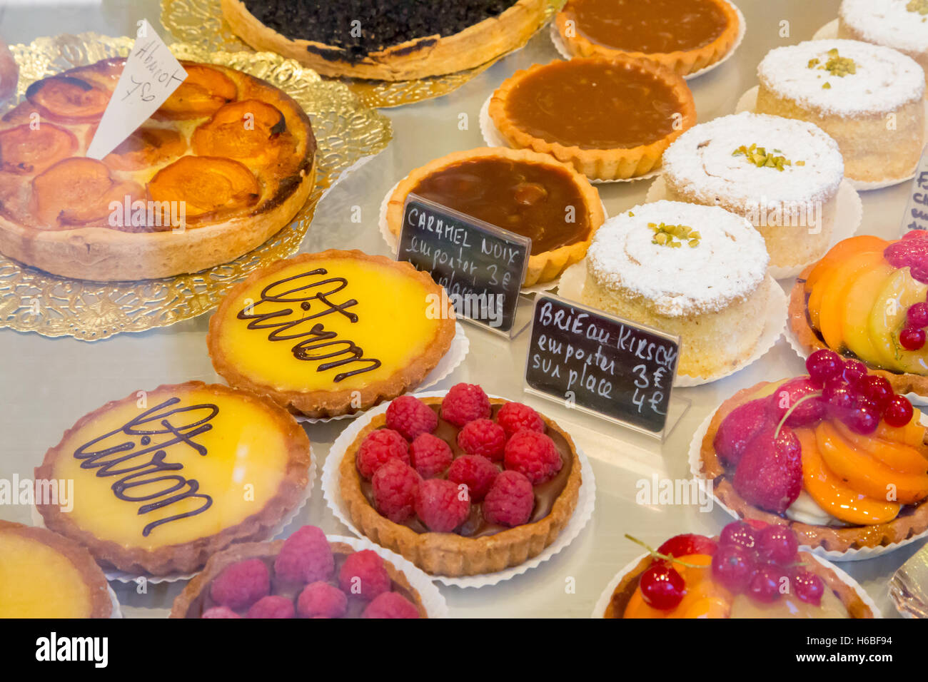 Tarts in a French patisserie shop window in Ribeaville, Alsace, France - Stock Image