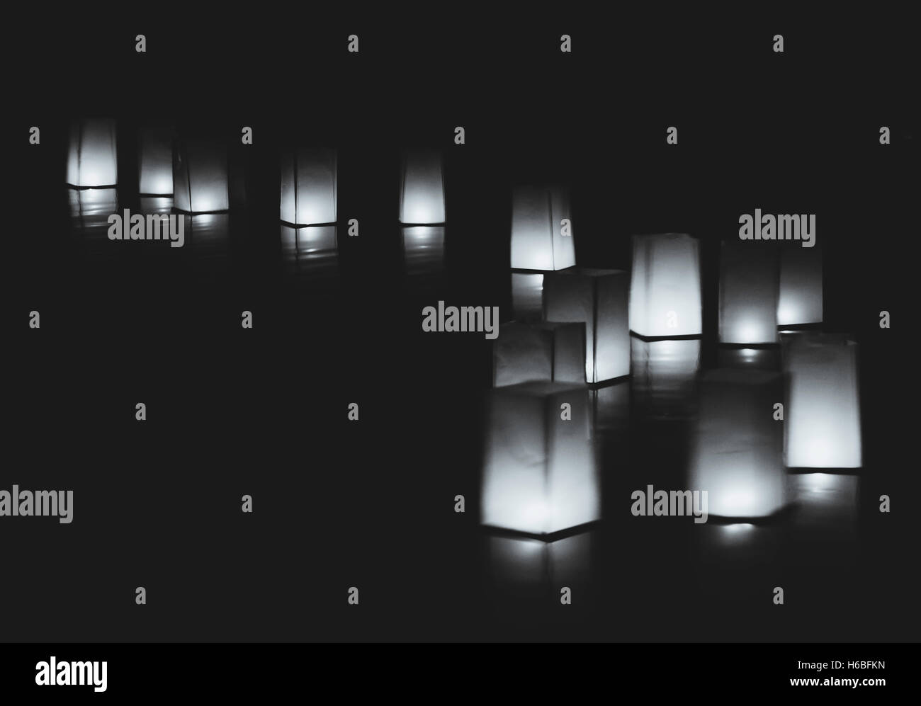 Hygge water floating candle lanterns in water at a wedding in California, black and white image. - Stock Image
