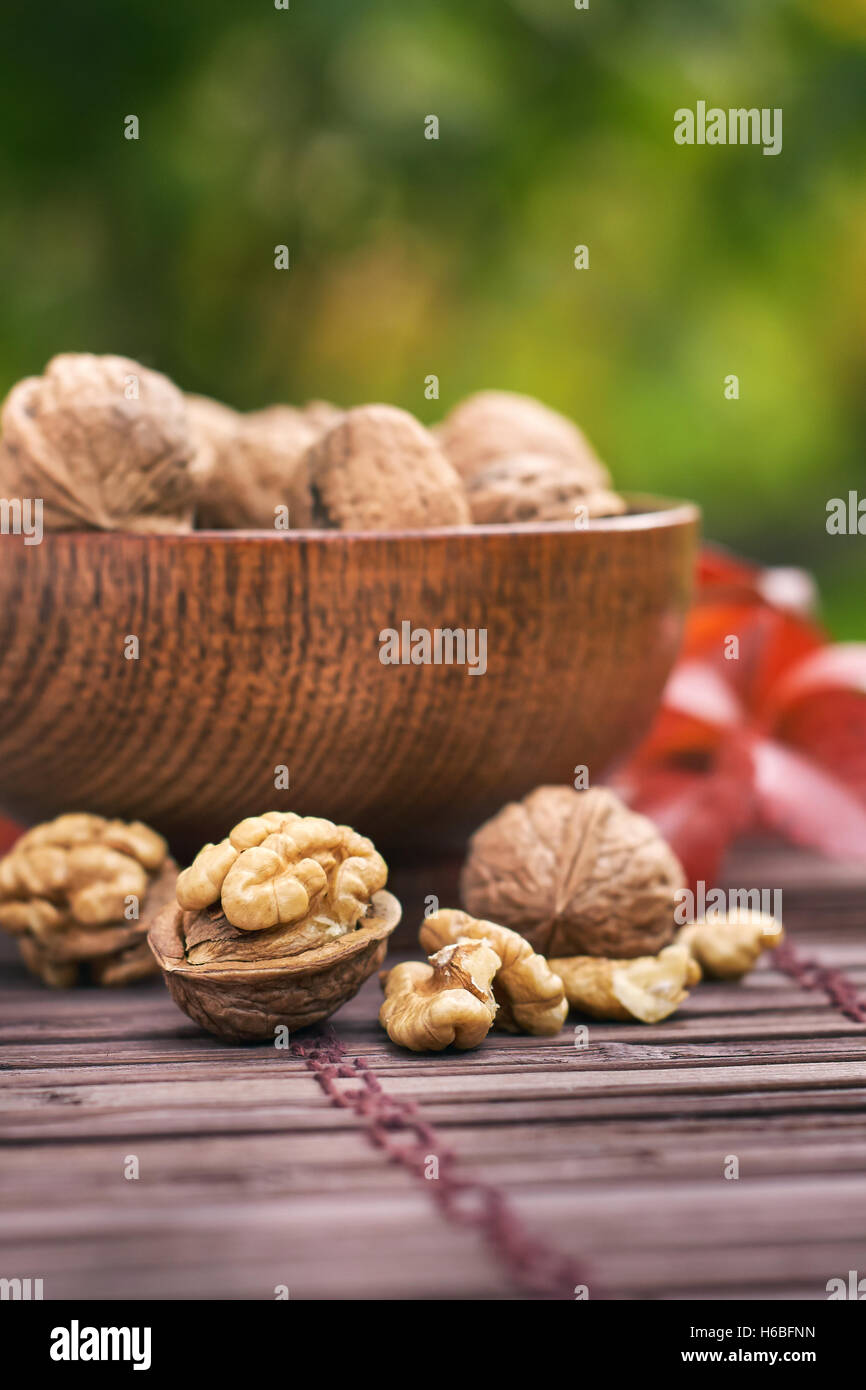 Walnuts in wooden bowl, green blurry background with plenty of copy space. - Stock Image