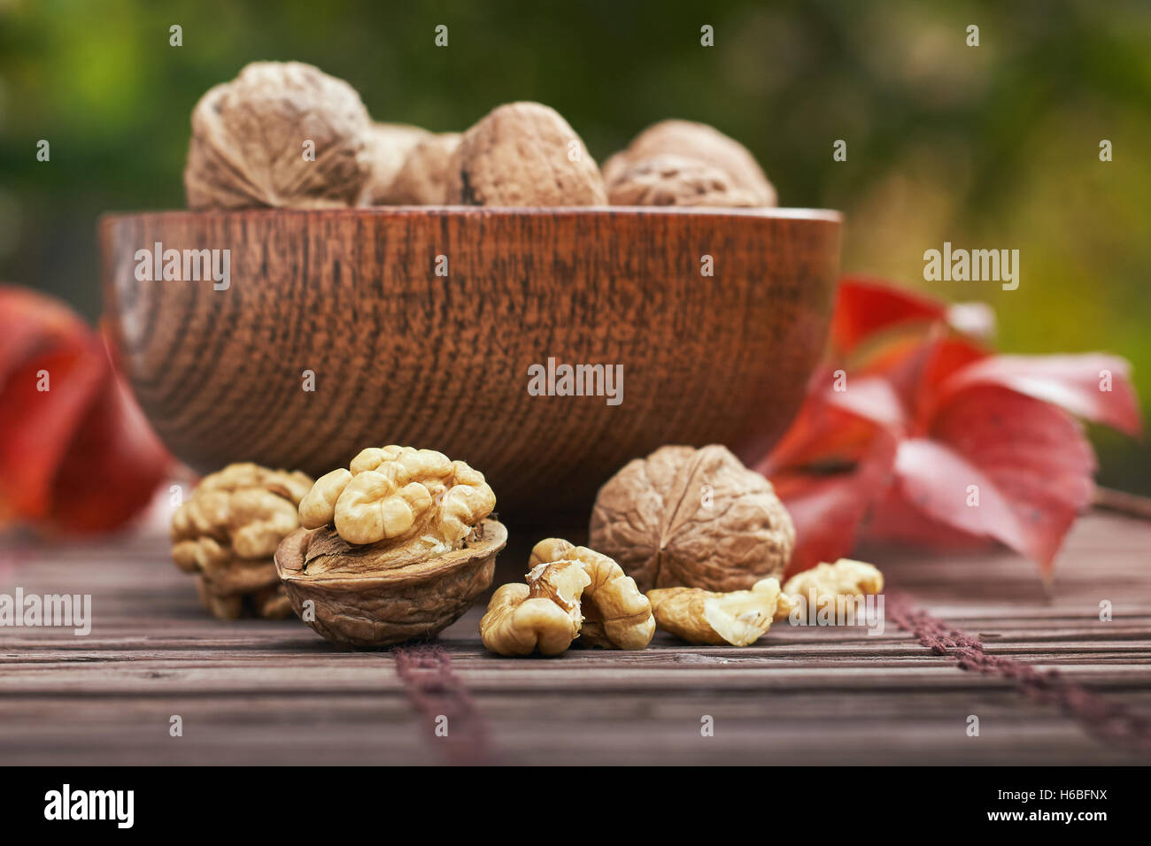 Walnuts in wooden bowl, green blurry background. - Stock Image