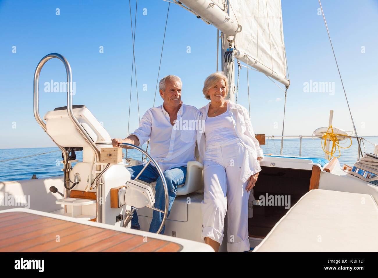 A happy senior couple laughing having fun sailing at the wheel of a yacht or sail boat on a calm blue sea - Stock Image