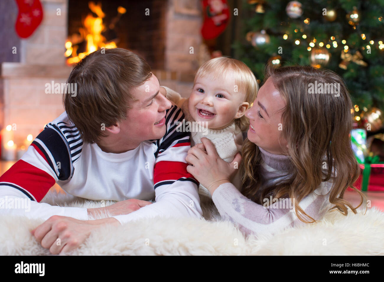 Happy family mother, father and baby little boy playing in the winter for the Christmas holidays Stock Photo