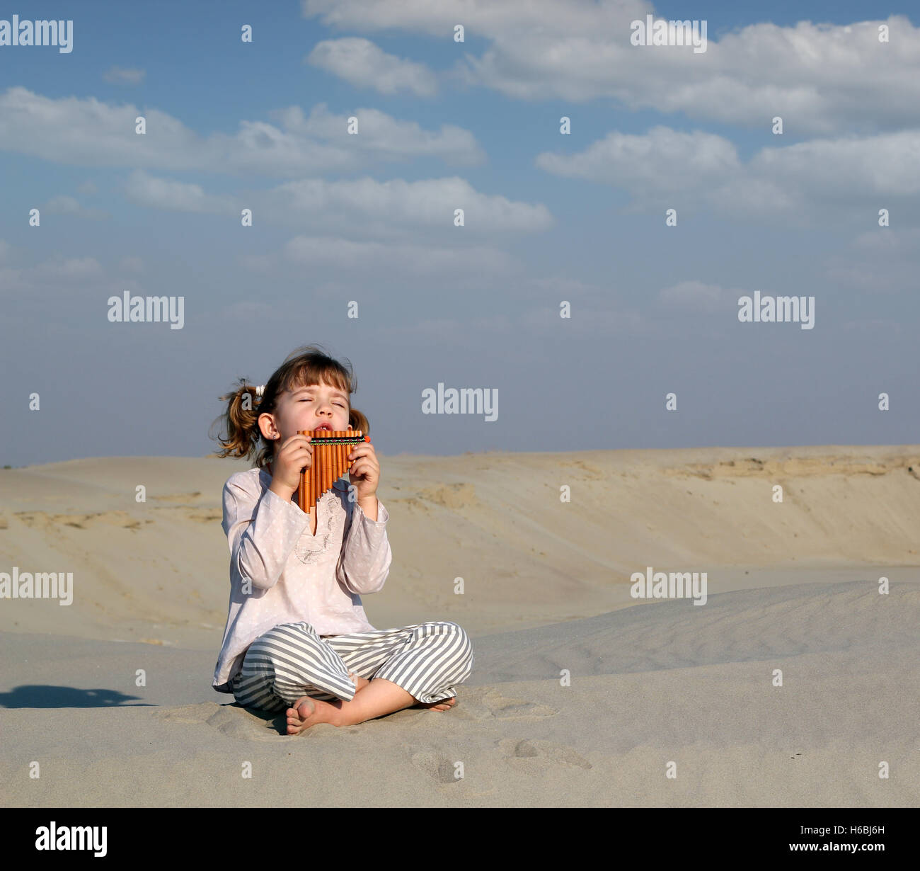 little girl play music on pan pipe in desert - Stock Image