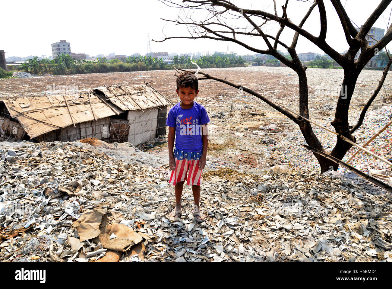 A Bangladeshi street children stand on the leather factories wastes dumped area at Hazaribagh Tannery area in Dhaka - Stock Image