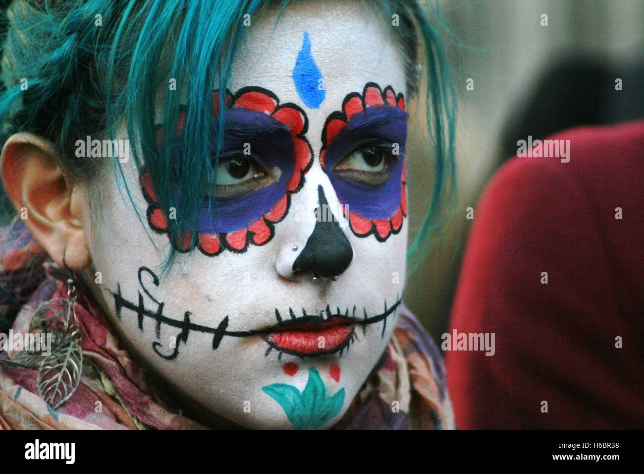 A protester paints her face in the style of the Mexican Day of the Dead, a celebration of the dead, during a protest - Stock Image