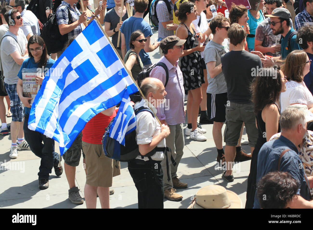 A protester holding the Greek flag, joins hundreds of other protesters in solidarity against the bailout conditions - Stock Image