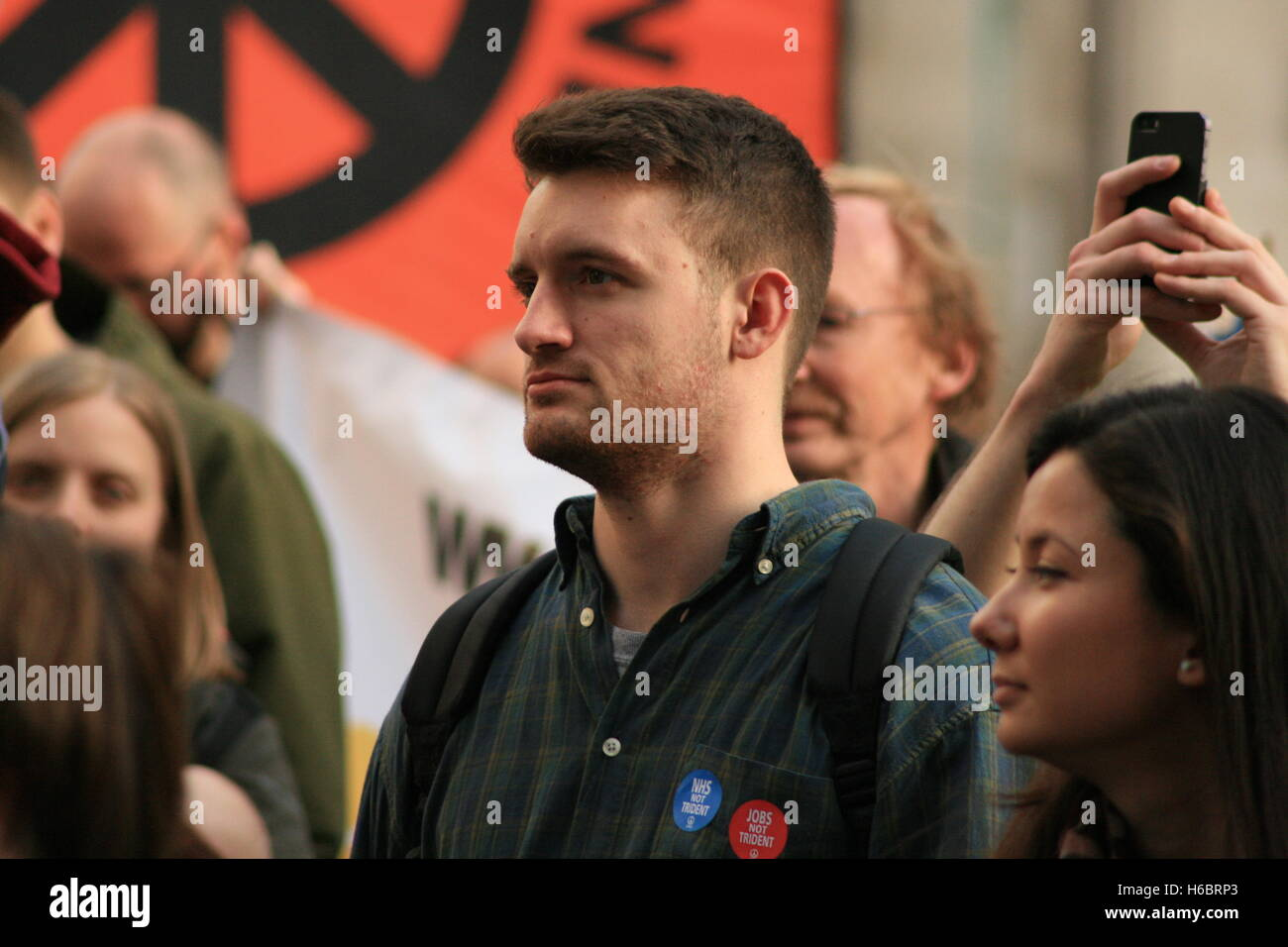 A protester against the renewal of the UK's nuclear weapons system Trident, listens to music and speeches at - Stock Image
