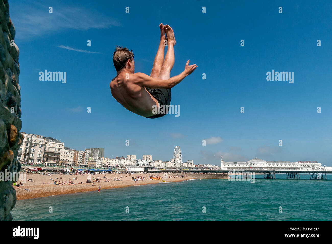 Boy diving into the sea on Brighton beach - Stock Image