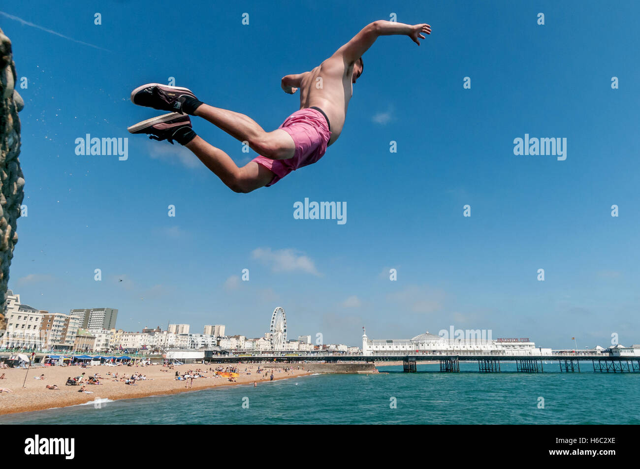 Boy diving into the sea on Brighton beach - Stock Image