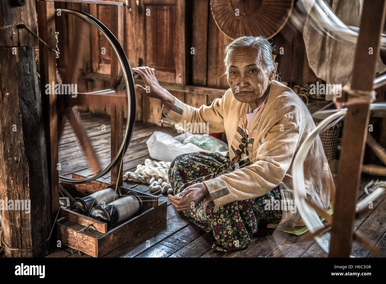 Woman worker weaves fabric in a weaving factory on Inle Lake. - Stock Image