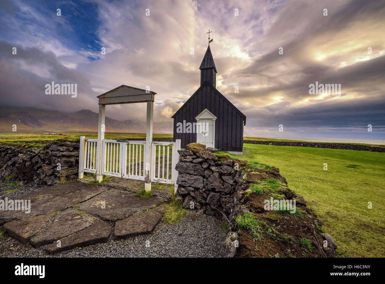 Entry gate and black wooden church of Budir in Iceland - Stock Image