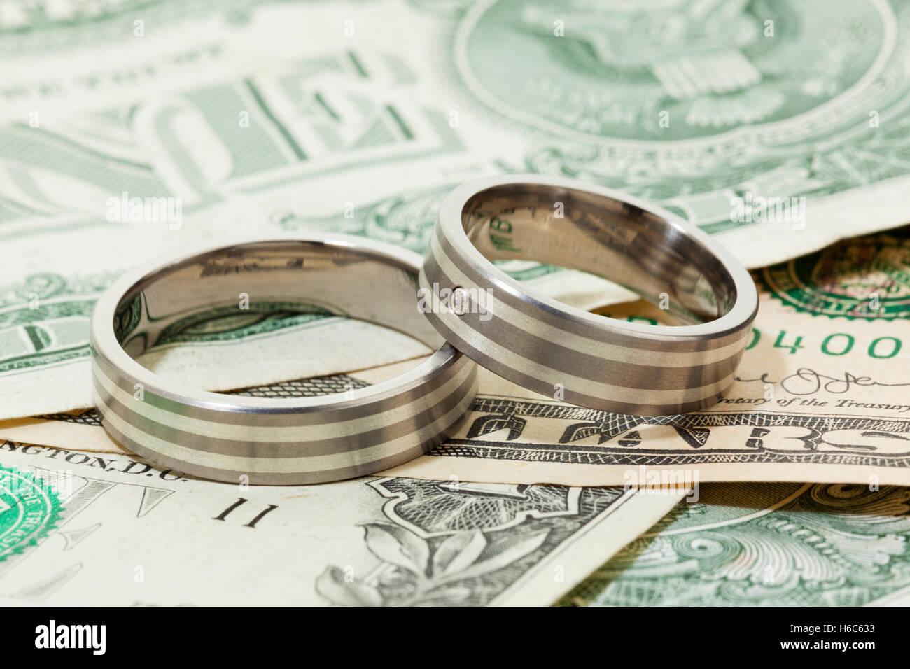 Pair of engagement or wedding rings on dollar bills - Stock Image