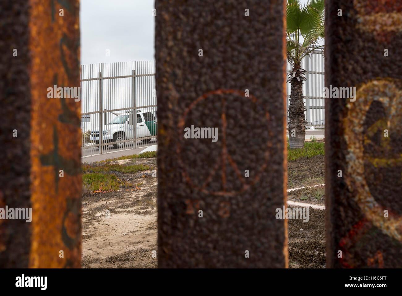 Tijuana, Mexico - A U.S. Border Patrol vehicle beyond two border fences near the Pacific Ocean. - Stock Image