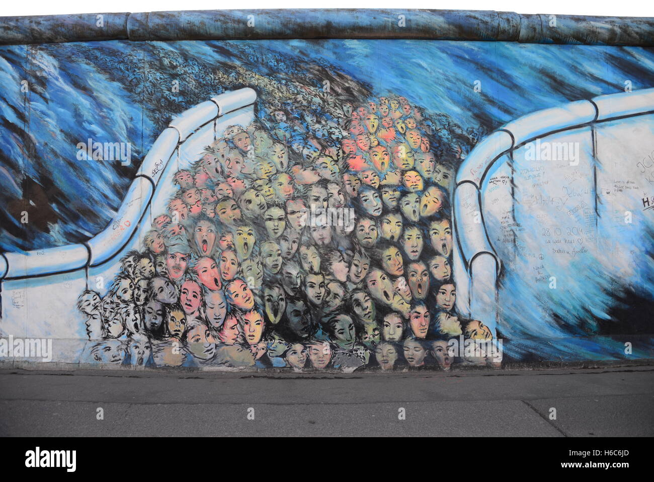 Part of the Berlin wall, bearing political and other graffiti and illustrations - Stock Image