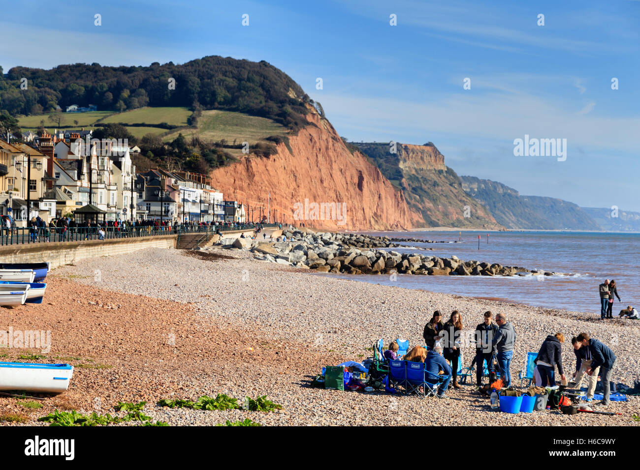 Visitors enjoying late October sun on the beach at Sidmouth, Devon, UK.  Town, esplanade and Jurassic Coast cliffs - Stock Image
