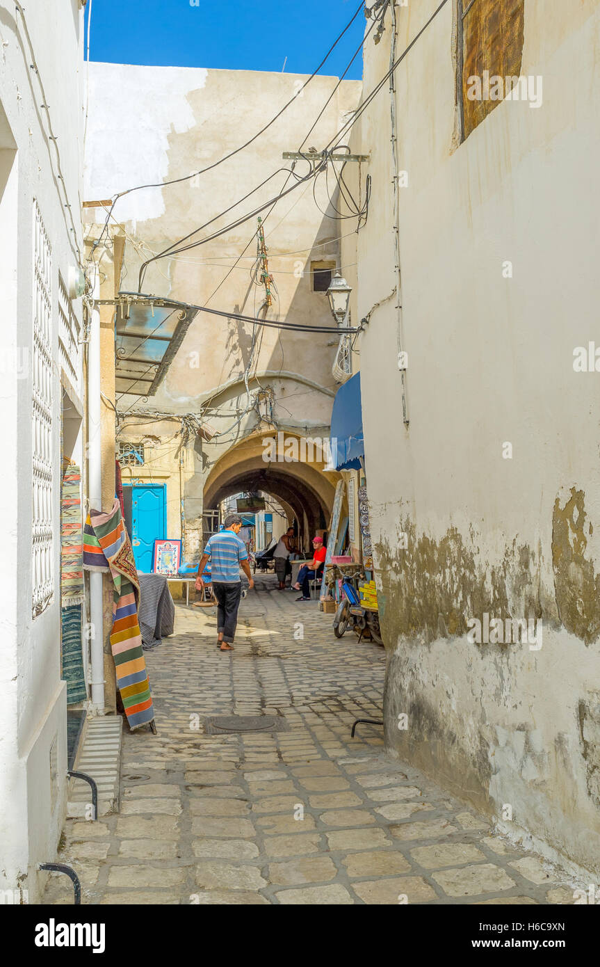 The narrow backstreet of Medina with tiny stalls and arched pass under the house - Stock Image