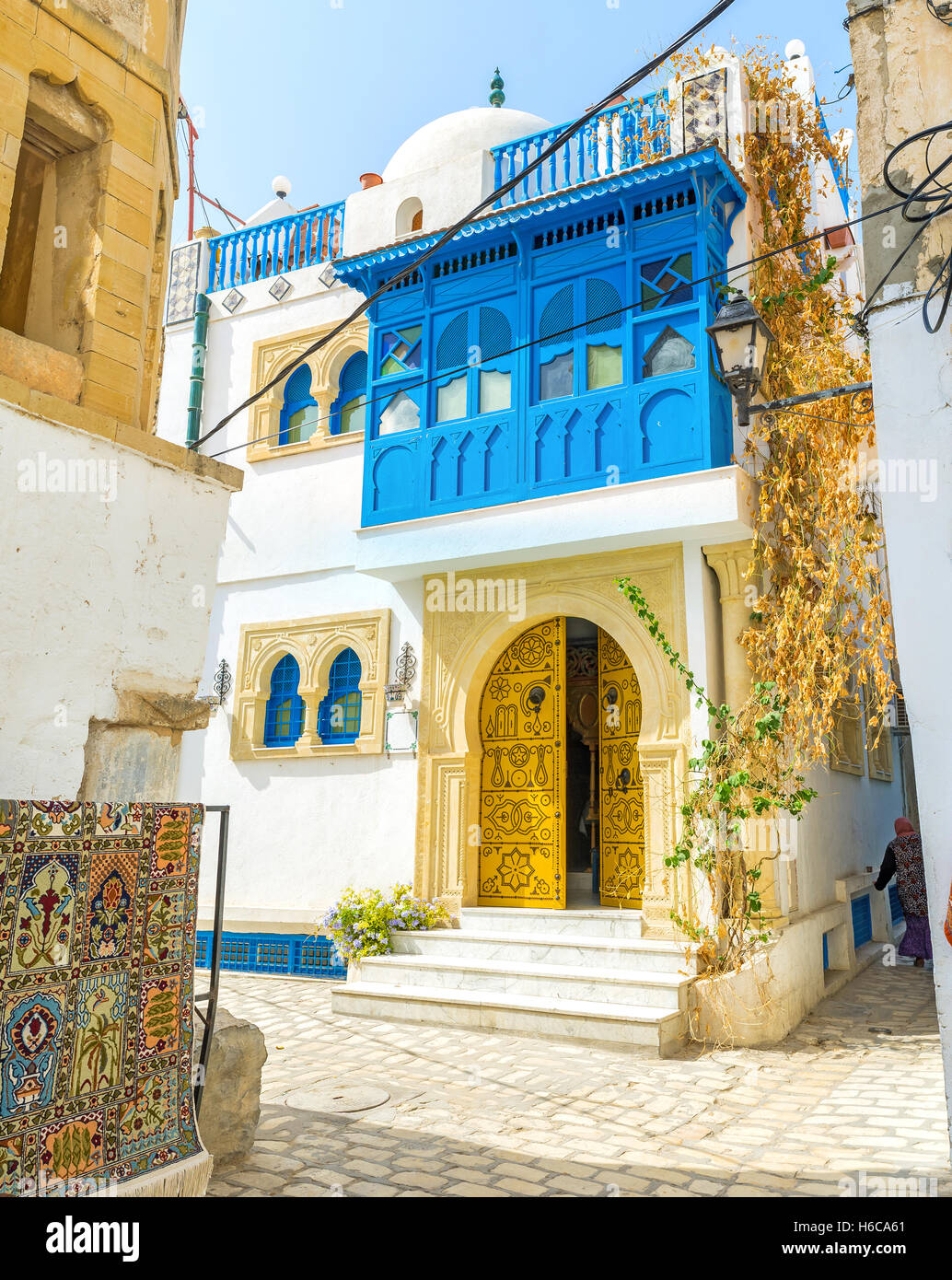 The white house decorated with the bright blue wooden balcony and yellow door with numerous rivets, Sousse, Tunisia. - Stock Image