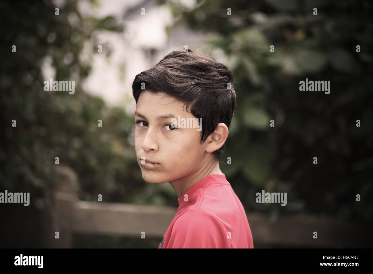 Portrait of young smiling boy - taken with vintage German lens.  Desaturated with added vignetting - Stock Image