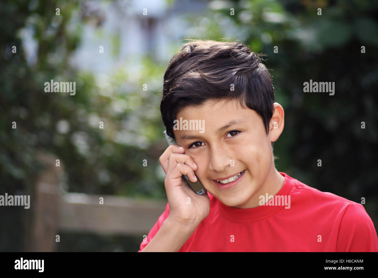Portrait of smiling Hispanic young boy with cell phone mobile - taken with vintage lens - Stock Image