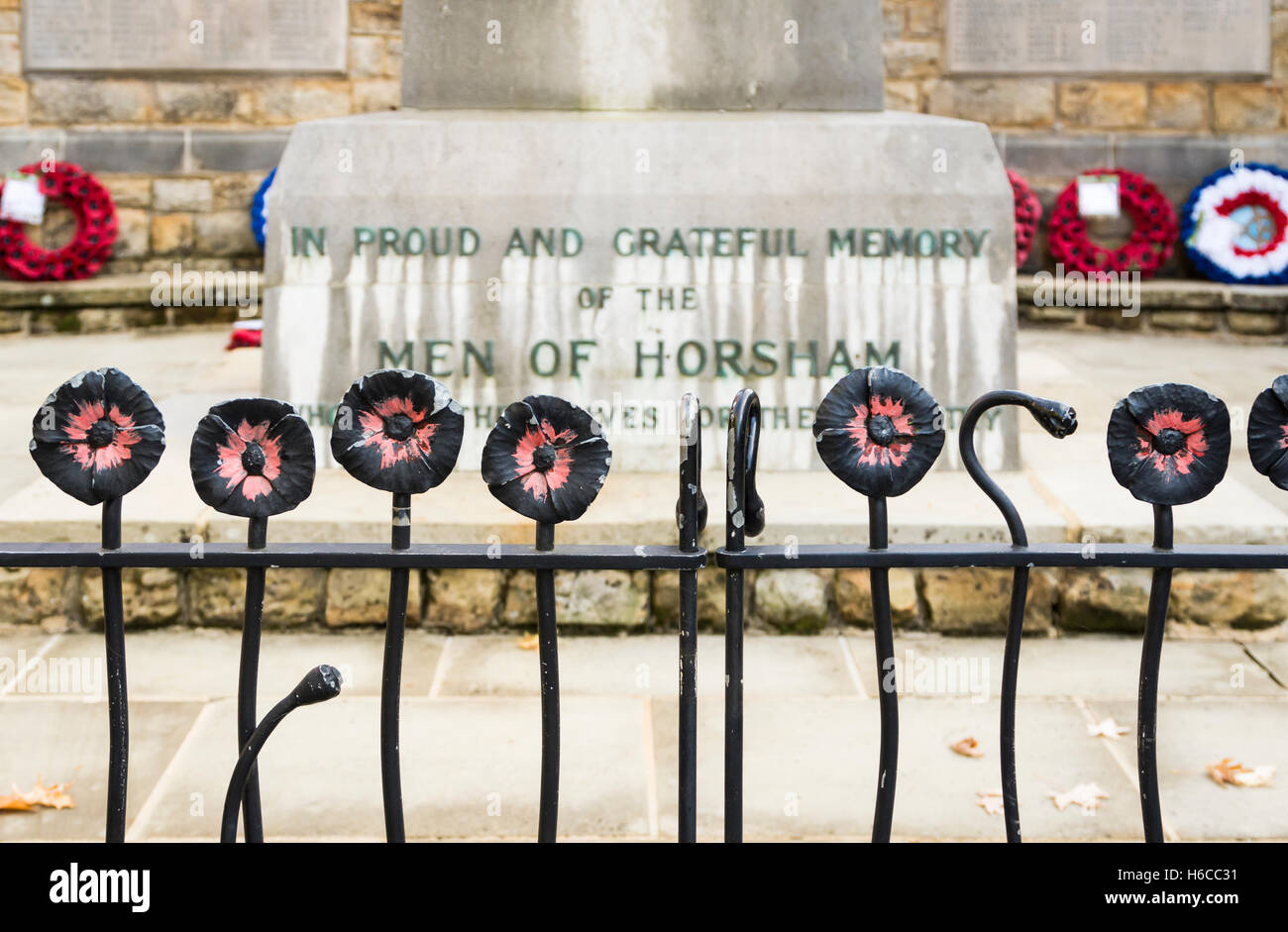 Decorative railings with wrought iron poppies surrounding the war memorial in Horsham, West Sussex, UK with poppy - Stock Image