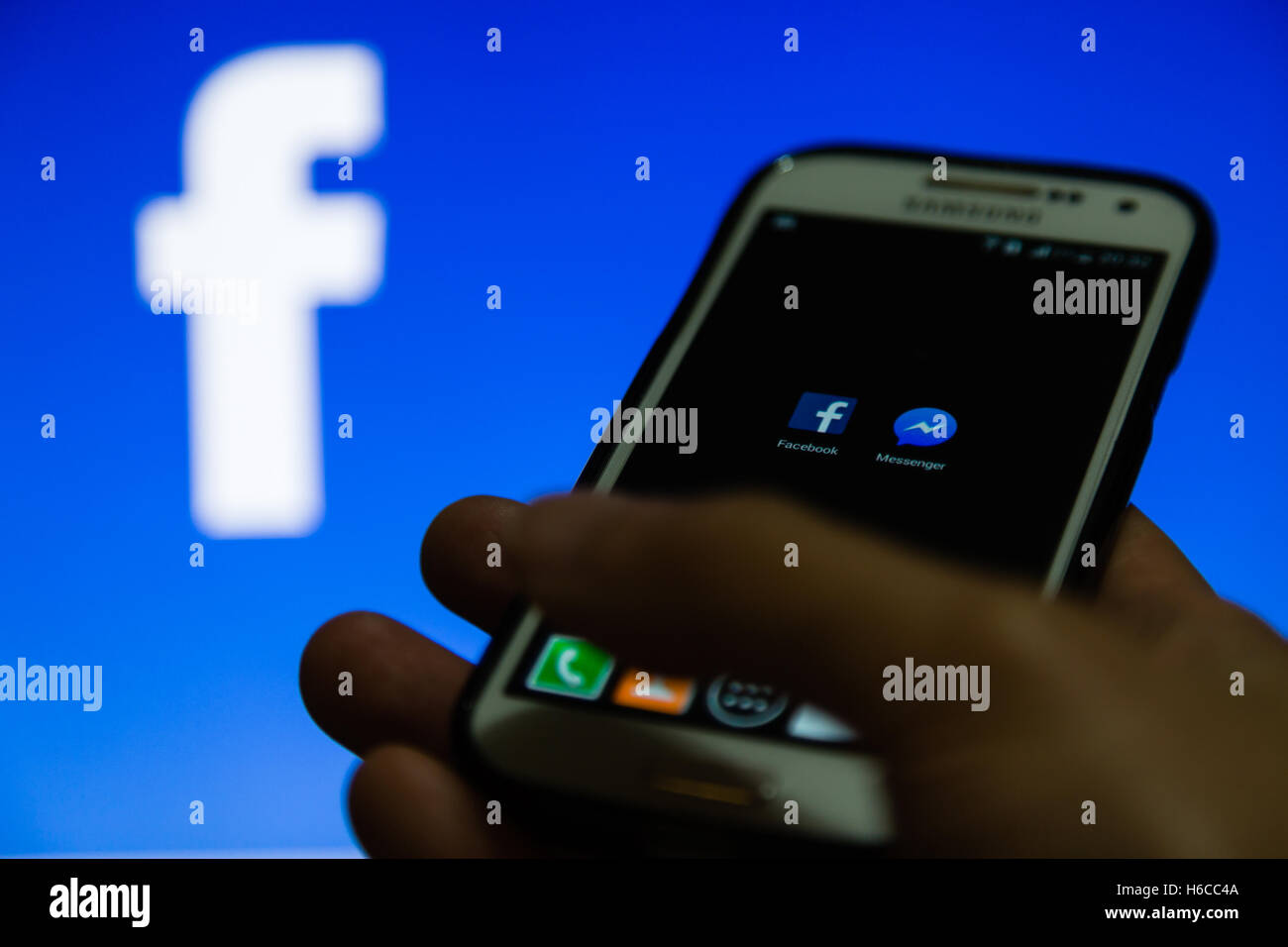 A smartphone display shows Facebook and Messenger application - Stock Image