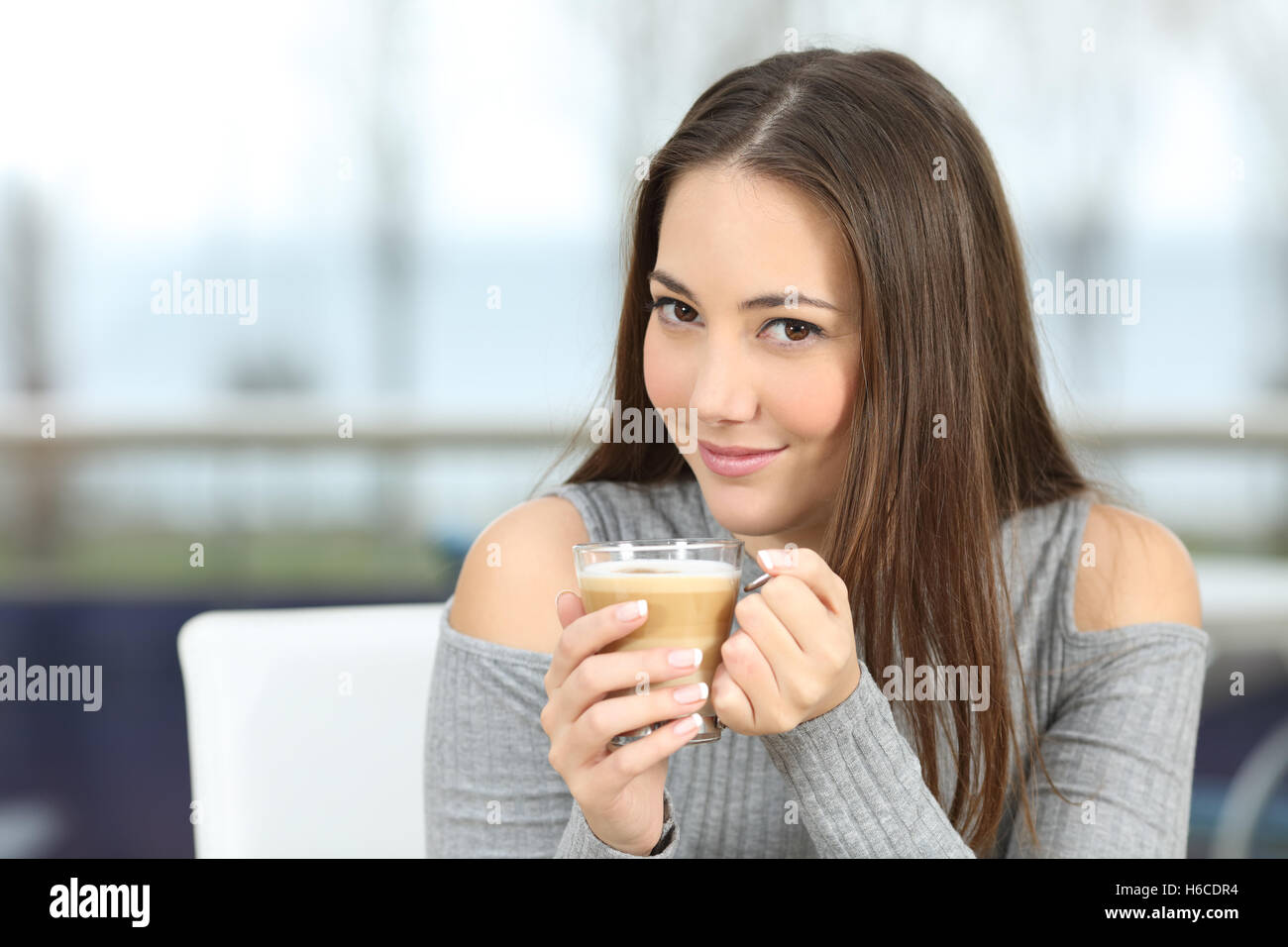 Confident woman posing looking at you holding a coffee cup in a restaurant with a window showing sea outdoors in - Stock Image