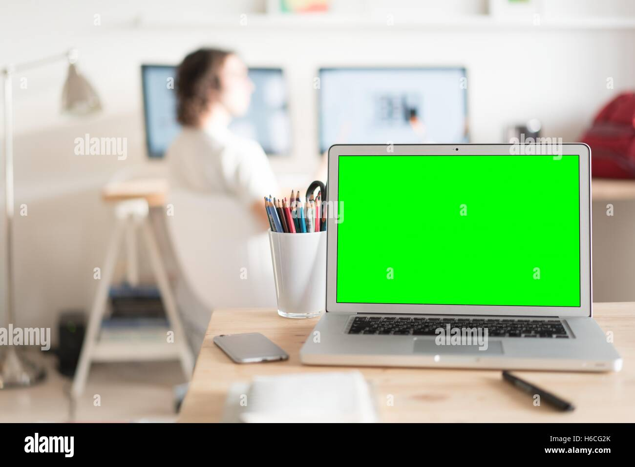 Green screen laptop computer and a glass with color pencils on ...