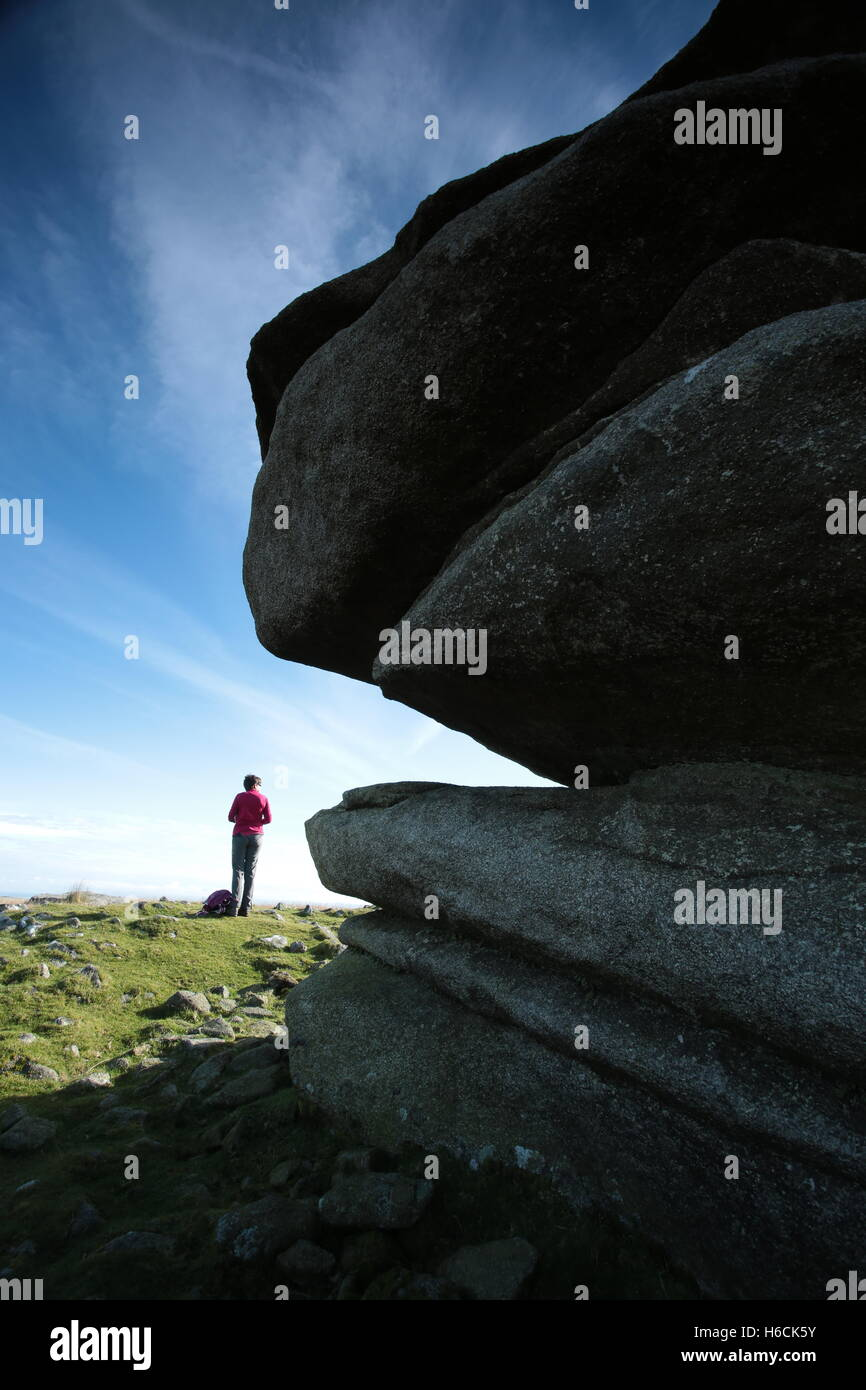 A woman standing by Showery tor,Bodmin moor. Stock Photo