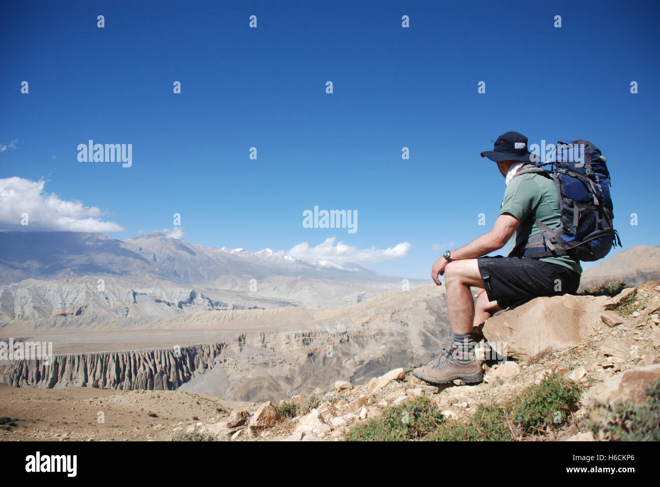 a trekker looks at the view in The Barren mountain landscape of the remote Damodar Himal in the Mustang region of - Stock Image