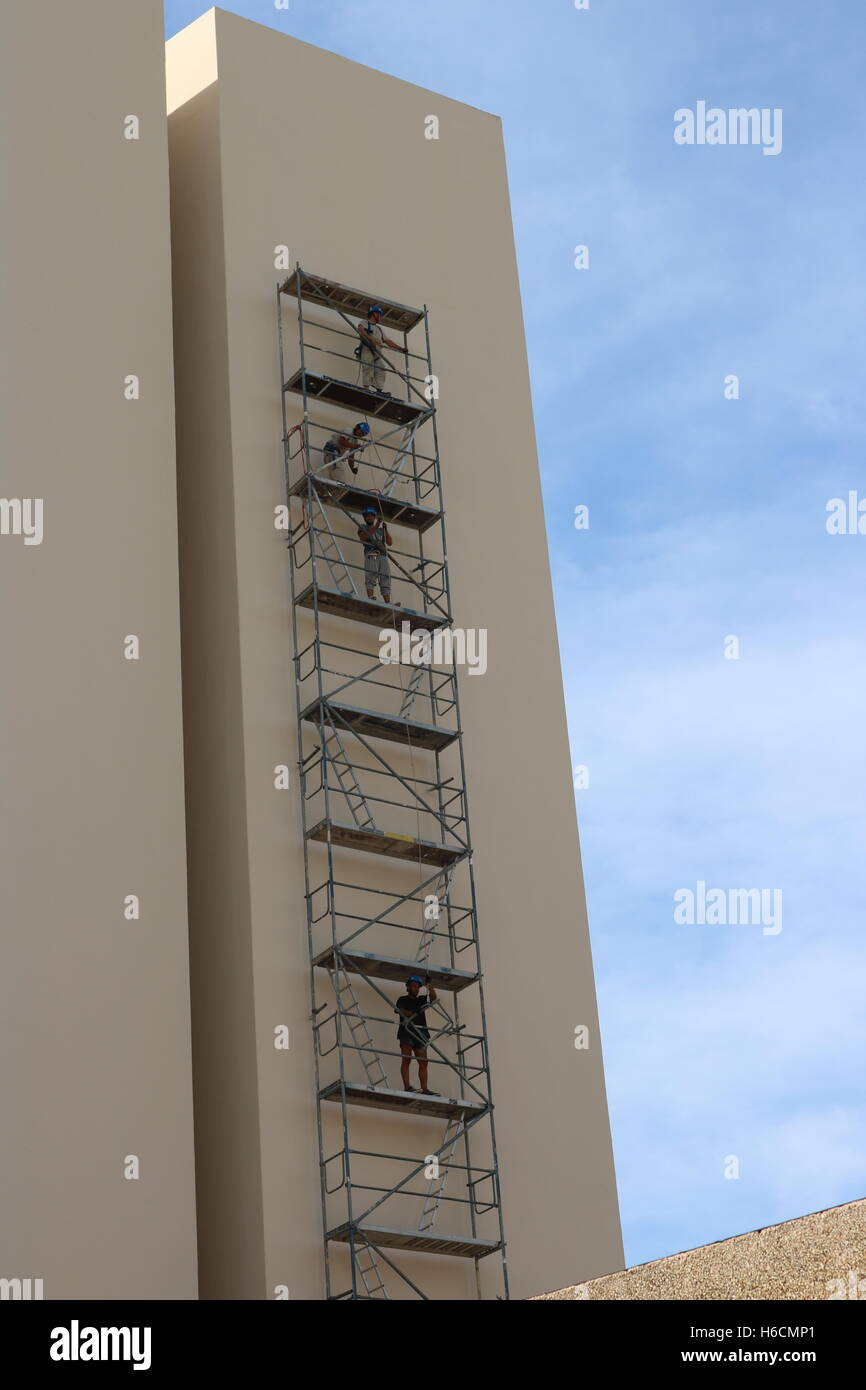Men on a scaffolding tower against a block of flats. - Stock Image