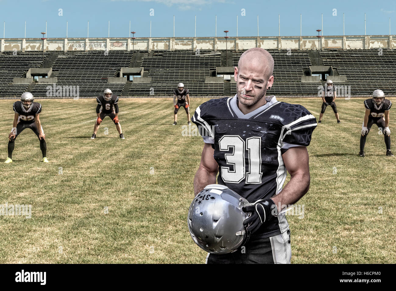 Portrait of a serious looking american football player, who stands  in a desolate stadium. - Stock Image
