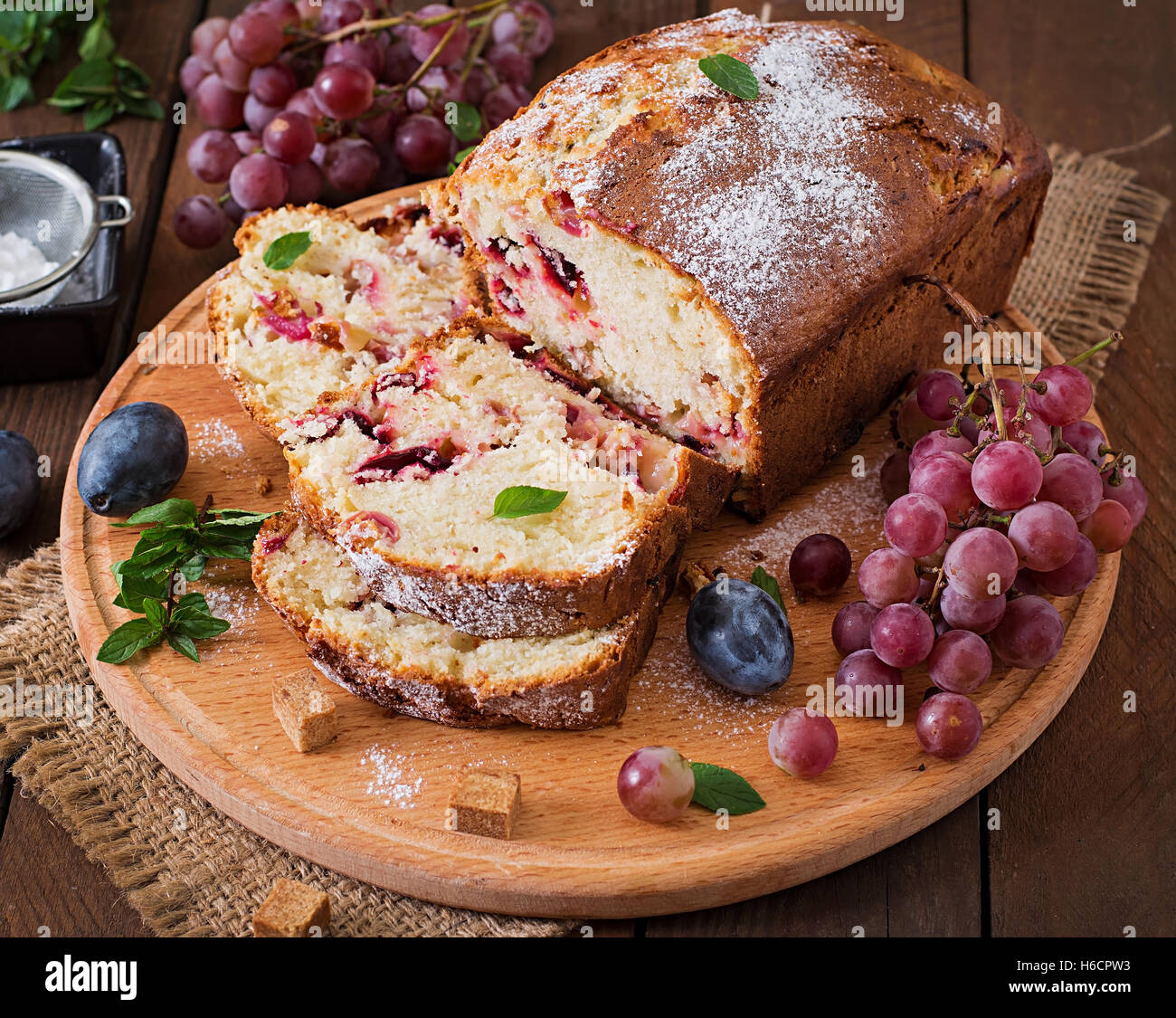 Juicy and tender cupcake with plums and grapes Stock Photo