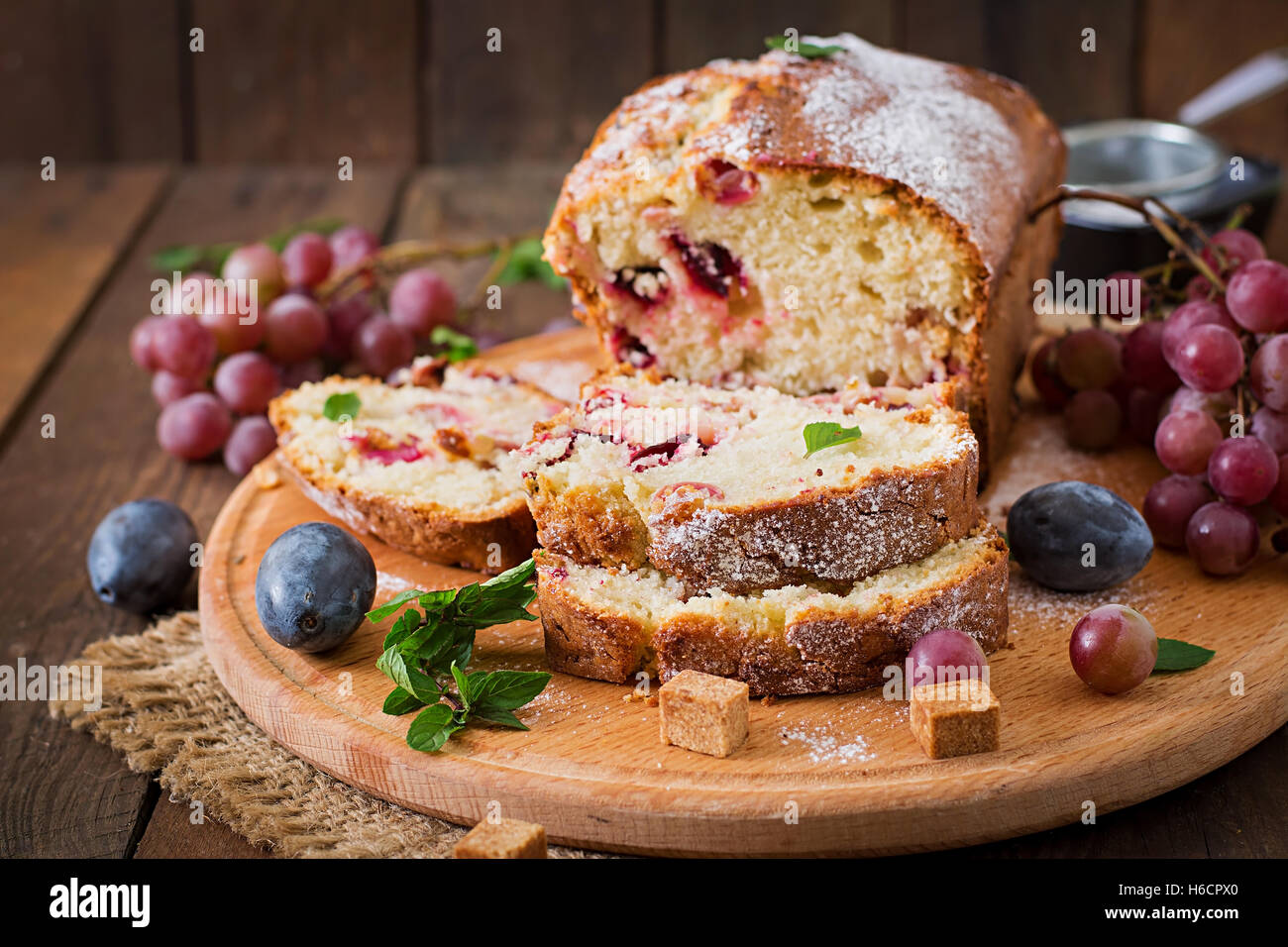 Juicy and tender cupcake with plums and grapes - Stock Image