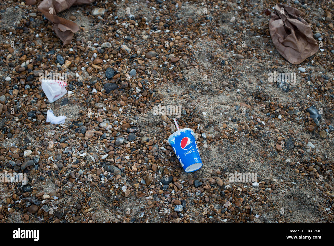 Discarded fast food packaging and a Pepsi plastic cup littering a beach. - Stock Image