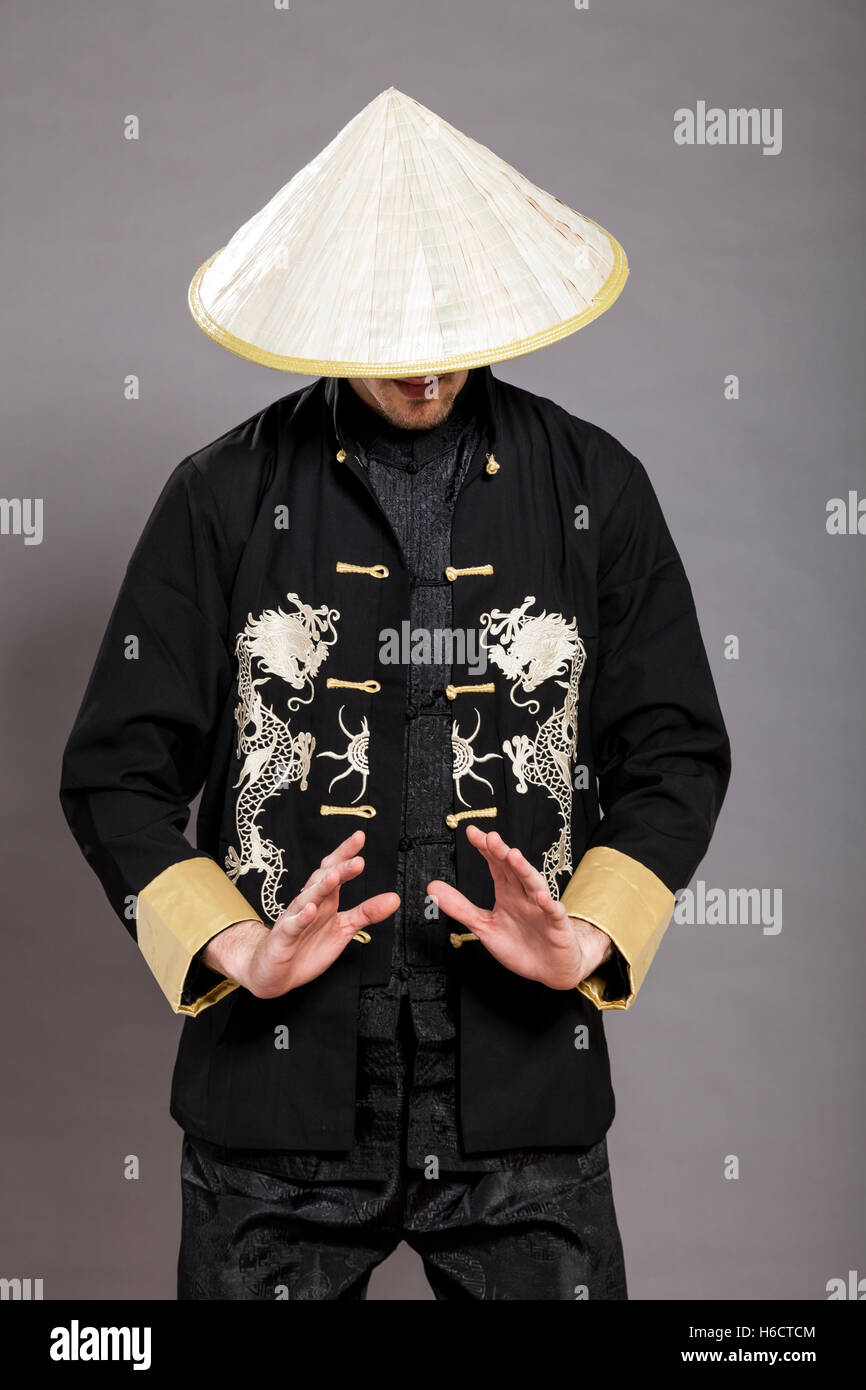 Studio shot of a man in his late twenties, wearing traditional chinese clothing and Kung-Fu posture; identity hidden. - Stock Image