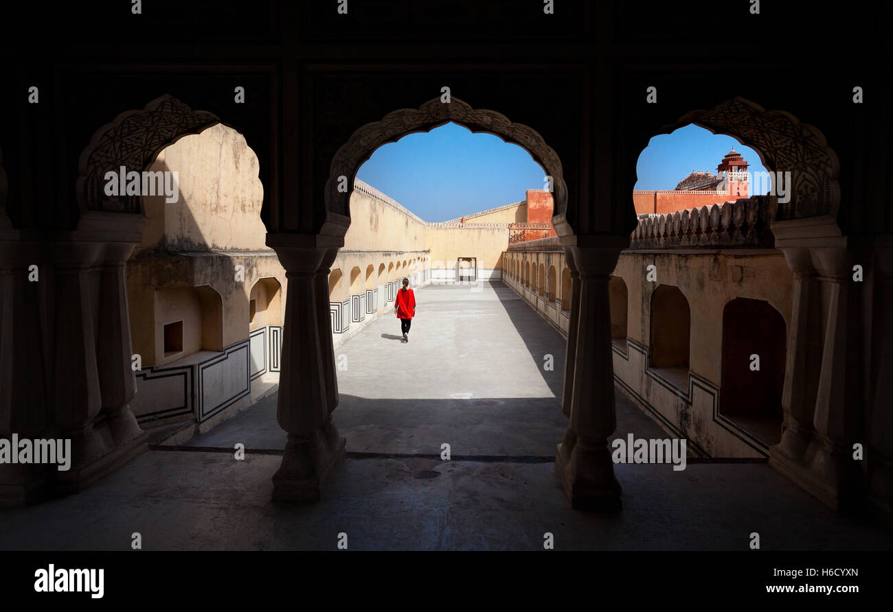 Woman in red dress walking in the palace Hawa Mahal with arch silhouette, Rajasthan, India - Stock Image