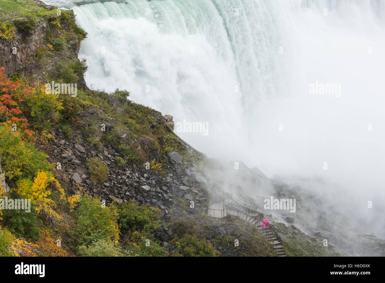 People in rain ponchos brave the mist and spray from the American Falls on the walk to the Crows Nest in Niagara Stock Photo