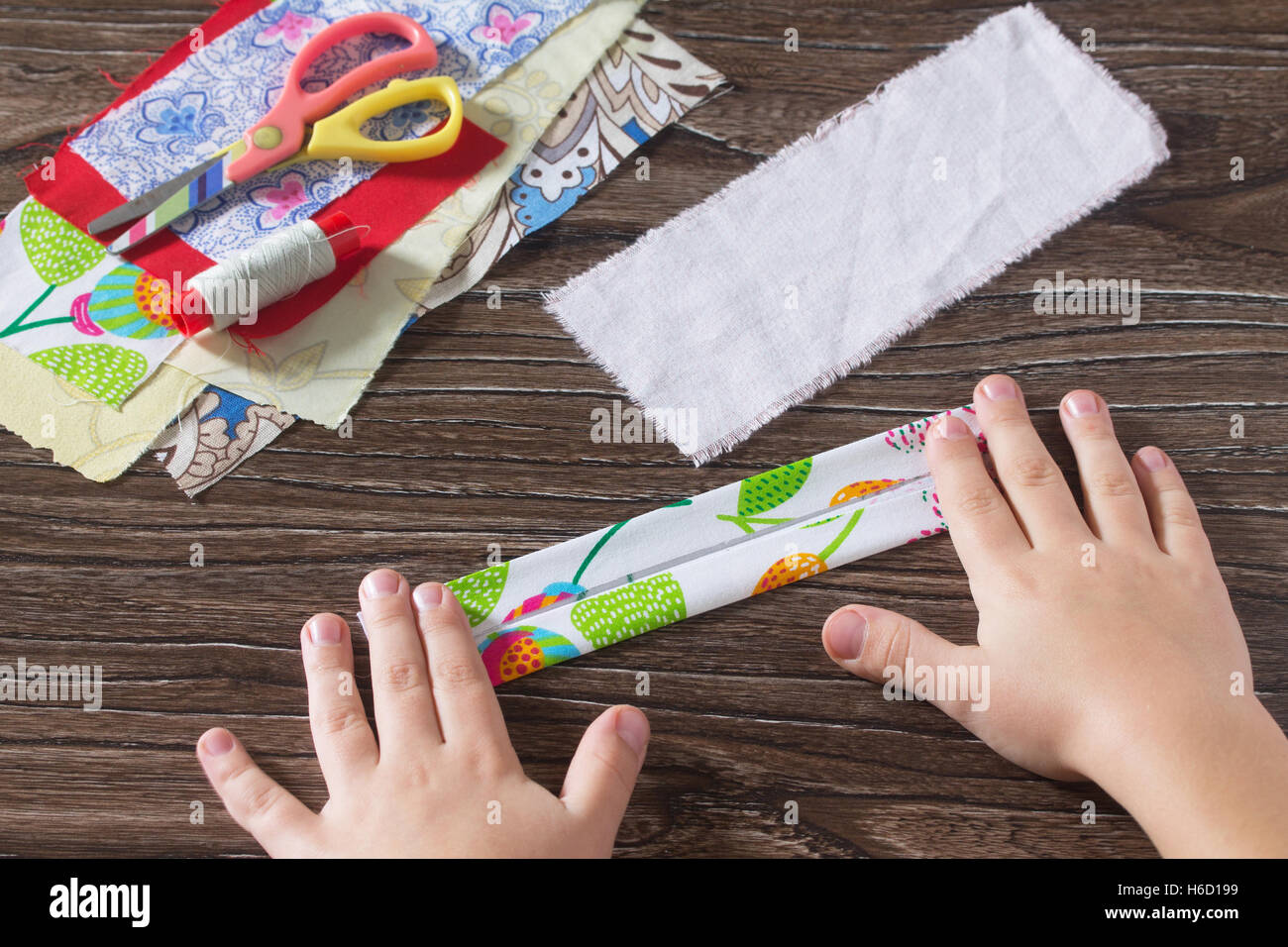 The child fold the strips of tissue. Protective amulet, textile doll Traditional Russian. Sewing crafts. - Stock Image