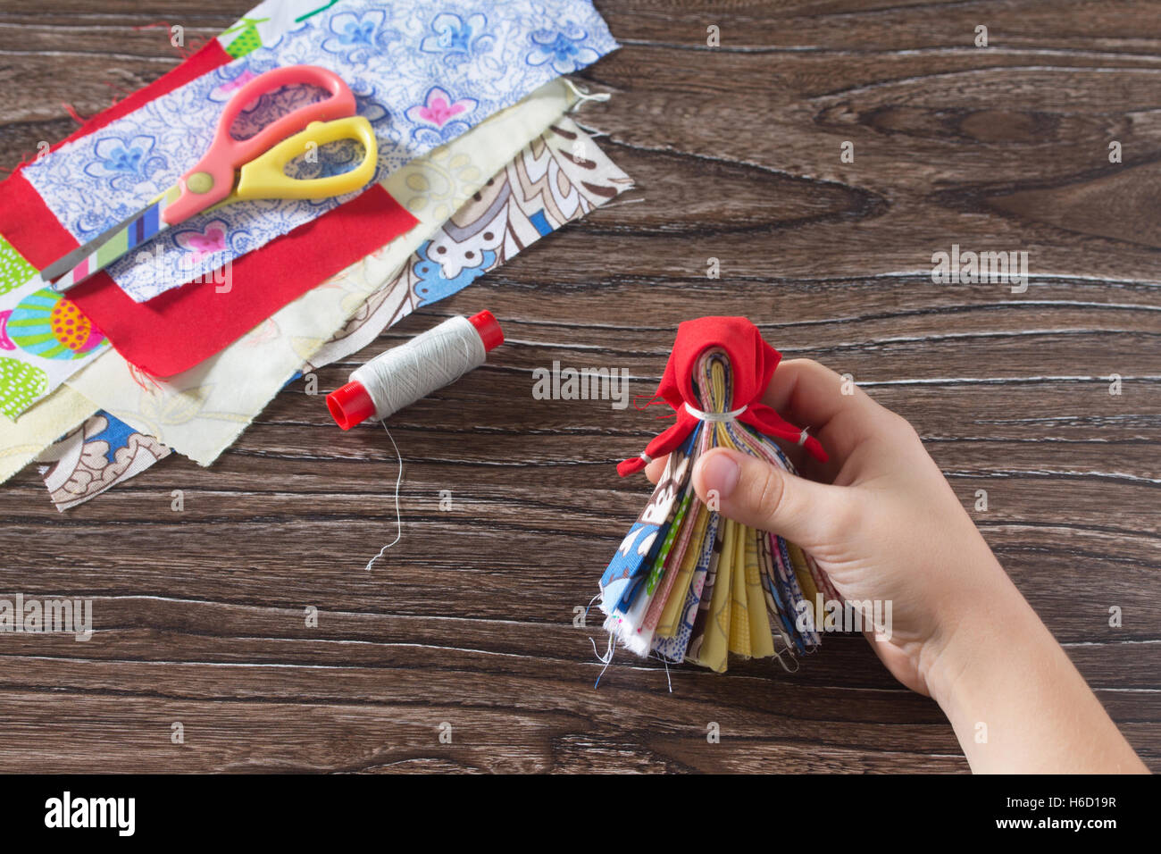 Protective averter, textile doll Traditional Russian. Strips of fabric, thread, scissors on wood background. Sewing - Stock Image