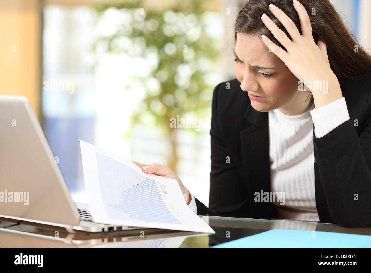 Worried businesswoman in bankruptcy watching decreased sales statistics in a paper document at office - Stock Image