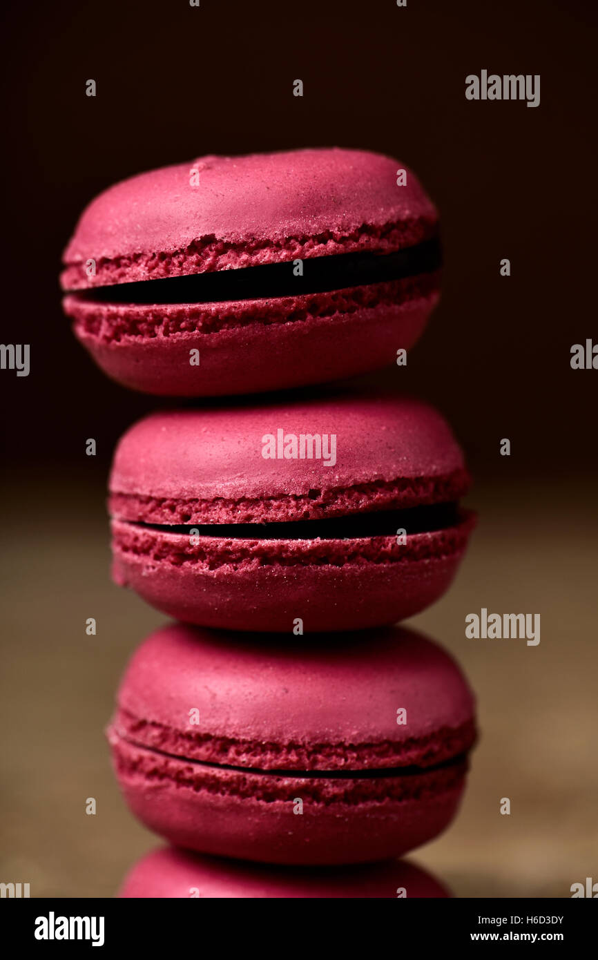 closeup of a stack of appetizing red macarons, with a retro effect - Stock Image