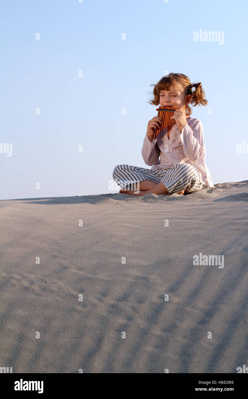 happy little girl play pan pipe in desert - Stock Image