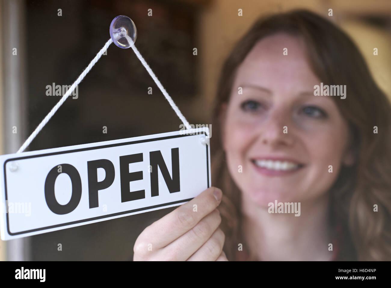 Store Owner Turning Open Sign In Shop Doorway Stock Photo